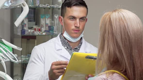 Thumbnail for Young Male Dentist Talking To His Female Patient, Examining Medical Papers