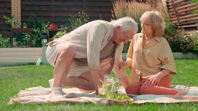 Senior Couple Resting In Backyard In Summer