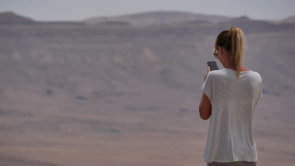 Thumbnail for Young Woman Taking Panoramic Photo of the Desert Crater on Her Phone