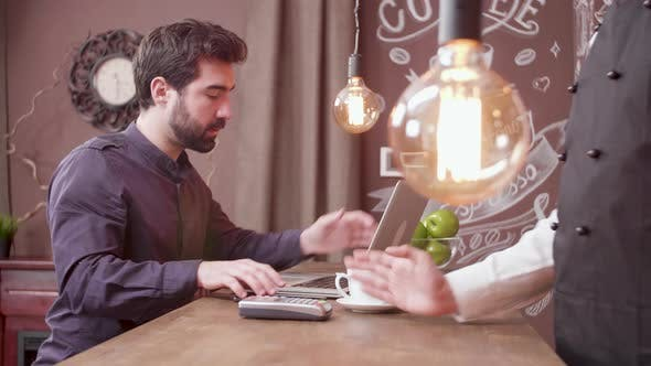 Thumbnail for Young Man Using His Smartphone To Make a Payment at a Bar Counter and Leaves