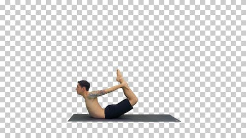 Sporty muscular young yogi man doing backbend exercise