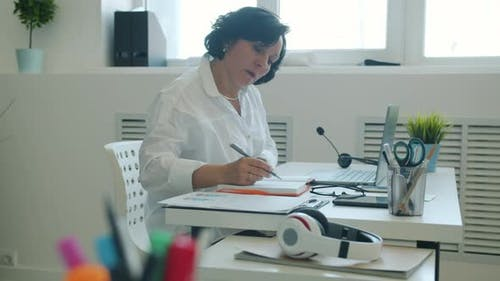 Slow Motion of Ambitious Businesswoman Working with Laptop and Writing in Notebook in Office