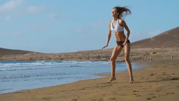 Cover Image for Girl in Sportswear Shorts and T-shirt Performs Jumps with Squats on the Beach Near the Ocean in the