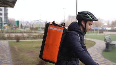 Food Courier Riding Bike and Entering Building
