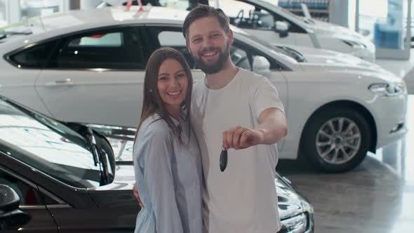 Thumbnail for The Concept of Buying or Renting a Car, Young Happy Interracial Couple with New Car Keys
