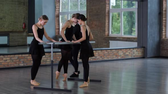 Diligent Ballerinas Warming Up at Ballet Barre