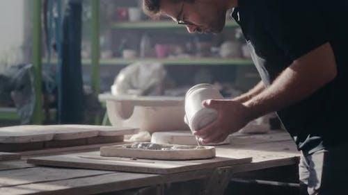 Male Ceramist Painting Handicraft in Studio
