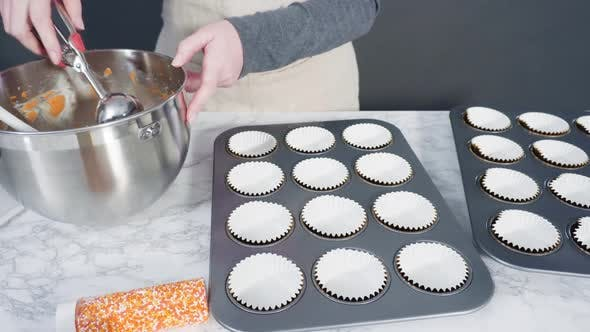 Thumbnail for Time lapse. Scooping pumpkin spice cupcake batter with batter scoop into a cupcake pan with liners.