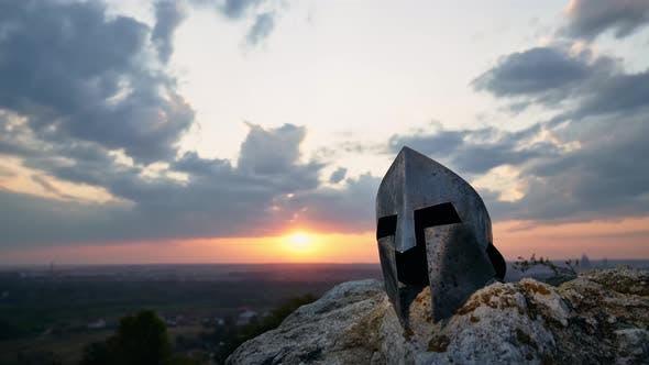 Antike Helm, bewölkter Sonnenuntergang im Hintergrund.