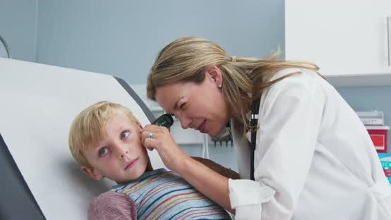 Woman pediatrician examining ears of young boy in clinic exam room