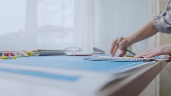 A young woman works and studies architecture from blueprints. She draws with a pencil in a notebook