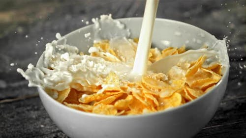 Super Slow Motion Stream Milk Pours Into a Plate of Cornflakes