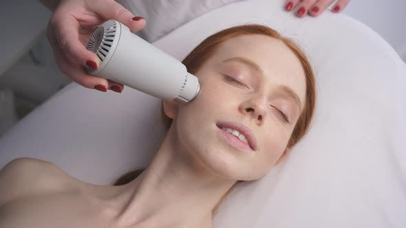 Beautiful Woman at a Cosmetologist's Reception Receives a Vacuum Massage of the Skin of the Face