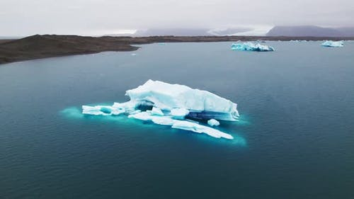Breathtaking Drone Shot of an Immense Iceberg Surrounded By Sea Water