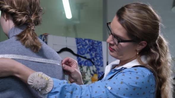Fashion Designer Taking Measurements of Customer