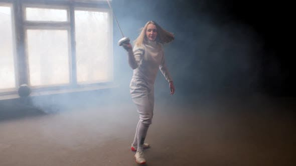 Thumbnail for A Young Woman Fencer with Loose Hair in White Costume Performing Basic Movements