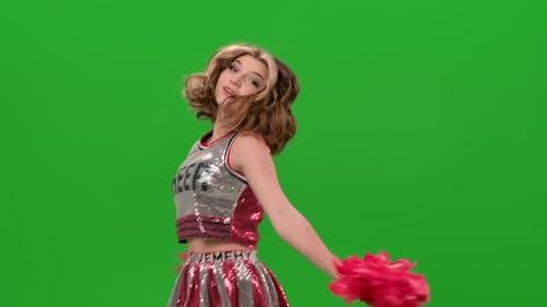 Eine entzückende Cheerleaderin in Uniform mit roten Pompons führt einen jubelnden Tanz