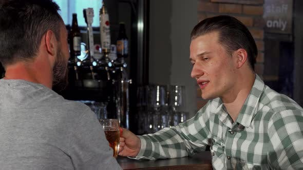Thumbnail for Young Man Enjoying Talking Over Glass of Beer with His Friend