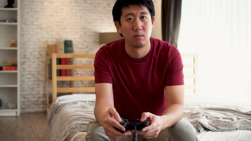Young Man Holding a Controller Playing Video Console Game