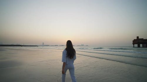 Back View of Woman in Elegant Clothes Walking in Water on Sand Beach with Dubai Cityscape in the