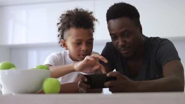 Teen Son and Dad Use Phone Together