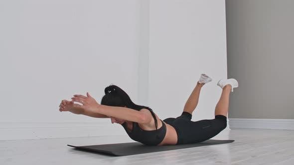 Young Attractive Woman in Double Leg Kicks Exercise Grey Studio