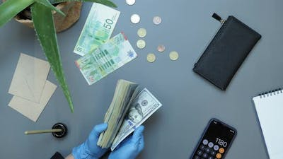 Counting money in protective gloves