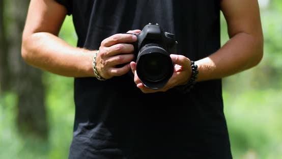 Man Photographer with a Photo Camera Configures Outdoor