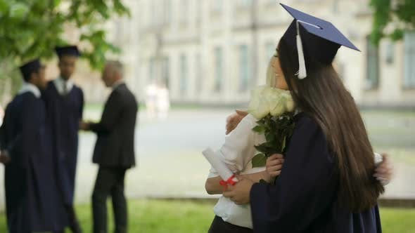 Thumbnail for College Female Graduate Waiting for Friend to Come Giving Flowers and Hugging