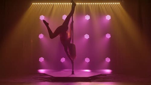 Beautiful Pole Dance Performed By an Athletic Young Female. Silhouette of an Attractive Body