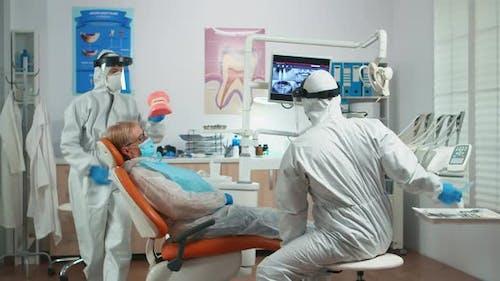 Dentist in Coverall Explaining Dental Hygiene Using Dental Skeleton
