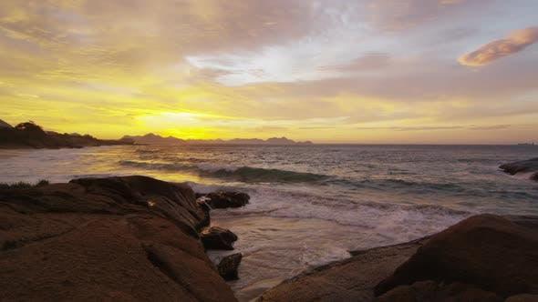 Tide washing over shore rocks at sunset