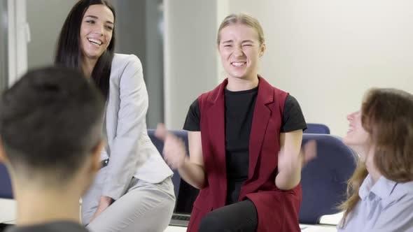 Fröhlich lachende Kollegen sitzen im Büro Reden