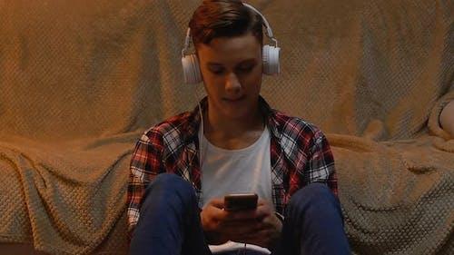Teenager hört Musik und benutzt Smartphone und hinterlässt die Rezension des neuen Albums