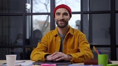 Smiling Bearded Man Posing on Camera at Desktop