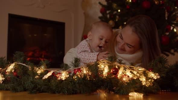 Mama und Baby spielen mit Weihnachtskugeln