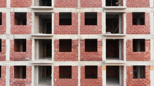 Exterior, non load bearing, red brick walls on a reinforced cement concrete frame of a building