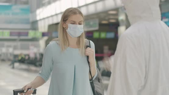 Portrait of Blond Caucasian Woman in Face Mask with Travel Bag Coming To Employee in Protective Suit