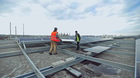 Thumbnail for Technicians installing solar panel on metal base