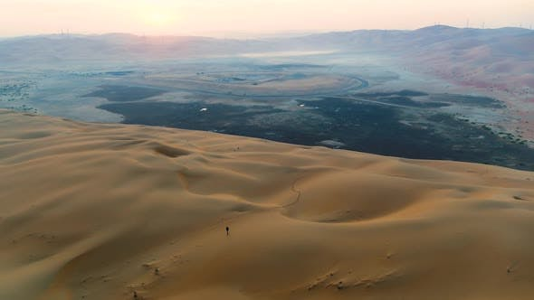 Thumbnail for Aerial view of a man walking alone in the top of dunes, U.A.E.