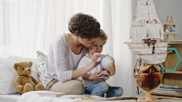 Thumbnail for Mother Showing Desk Globe to Son