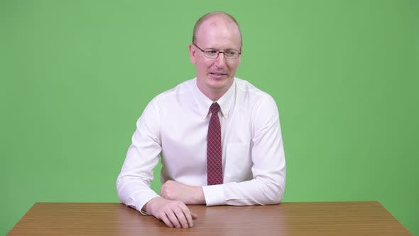 Thumbnail for Mature Bald Businessman Looking Bored Against Wooden Table