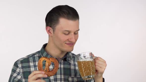 Thumbnail for Young Attractive Man Laughing Joyfully Sipping Delicious Beer Holding a Pretzel