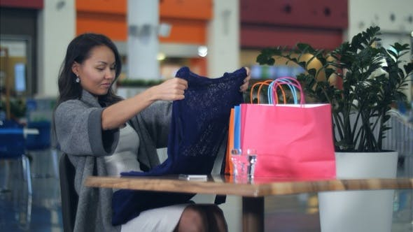 Thumbnail for Asian young women with shopping bags looking at new clothes