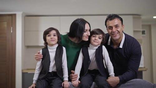Famille interraciale positive posant dans le salon à la maison