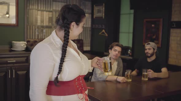 Thumbnail for Plump Woman with Pigtails in White Blouse and Corset Raising Glass of Beer Looking Towards Two Men