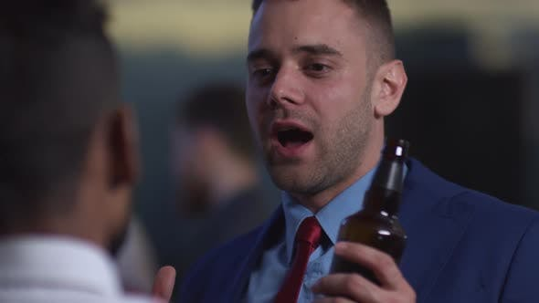 Thumbnail for Businessman Holding Beer and Talking to Colleague at Office Party