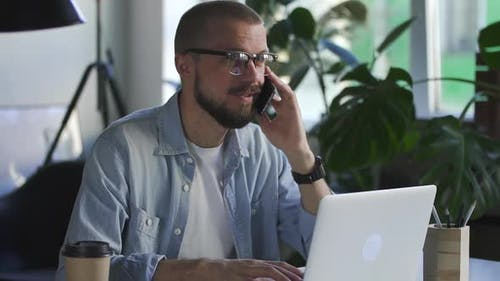 Handsome Man Accountant Talking on the Phone with Smile in Office with Laptop Computer