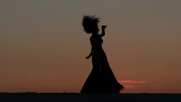 Thumbnail for Belly Dancing Against the Beautiful Sunset on the Beach. Silhouettes