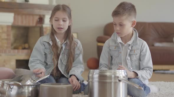Thumbnail for Portrait Cute Adorable Brother and Sister Twin Playing Musicians Beating the Pots and Dishes with
